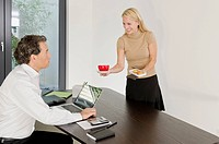 Woman serving coffee and pastry for businessman at desk