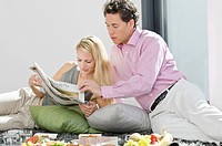 Couple having breakfast and reading newspaper on rug