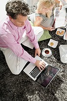 Couple on rug with food, magazine and laptop