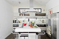 Modern kitchen with laptop and vegetables on counter