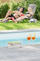 Couple relaxing in deckchairs by the poolside