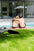Couple sitting by the poolside