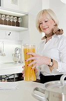 Senior woman holding Spaghetti glass in kitchen (thumbnail)
