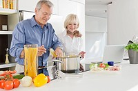 Senior couple preparing healthy pasta meal in kitchen