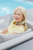 Smiling senior woman sitting on couch by the poolside