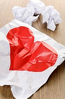 Red heart on a crumpled paper