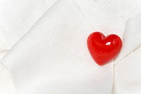 Red heart on white cloth
