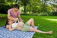 Man applying cream on stomach of pregnant woman