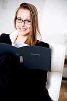 Smiling teenage girl holding application folder