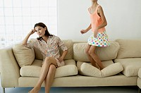 Mother Ignoring Daughter Jumping on Sofa