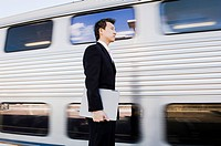 Businessman with Laptop at Train Station