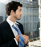 Businessman at Window Putting on Tie