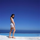 Woman Standing by Oceanfront Swimming Pool