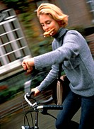 Young Woman Holding Sandwich on Bicycle