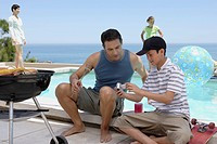 Father and Son Looking at Video Camera by Pool