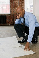 Businessman Looking at Blueprints in Empty Office