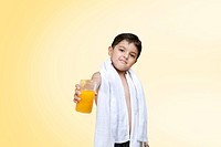 Portrait of boy holding glass of juice over colored background