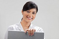 Portrait of modern businesswoman working on laptop