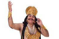 Man dressed as Raavan talking on a mobile phone