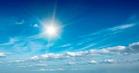 Sun with clouds in blue sky