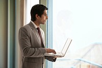 Handsome young businessman using laptop while looking outside