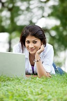 Portrait of woman lying on grass in lawn and using laptop