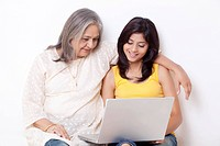 Teenage girl and grandmother using laptop