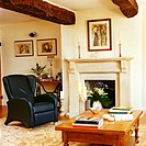 An elegant black armchair is placed next to the fireplace as wooden beams are seen at the ceiling