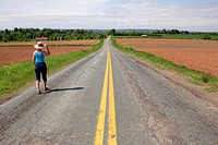 a woman walking along a road in the annapolis valley of nova scotia canada