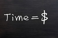 Time is money handwritten with white chalk on a blackboard