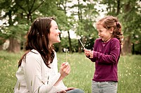 Mother with small daughter blowing to dandelion _ lifestyle outdoors scene in park