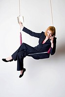 Businesswoman Hanging From a Trapeze