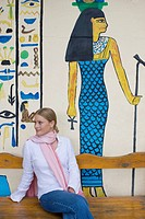 Tourist Sitting by Egyptian Style Mural