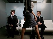 Businesswoman Walking Past Businessmen in Waiting Room
