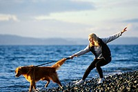 Woman Walking Golden Retriever next to Ocean