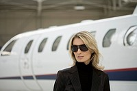 Woman in Sunglasses Standing by Plane