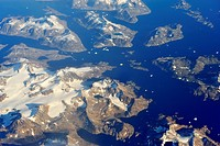 Snowy rocky islands and floating icebergs on Arctic Ocean
