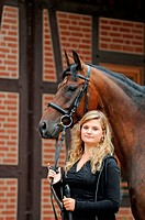 Young woman rider holding a Hanoverian Horse the reins while standing in front of a timber_framed house