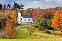 USA, Maryland, Country church sits among autumn leaves and next to country road