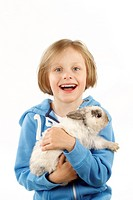 Laughing child holding a pet rabbit. Studio picture against a white background