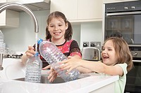 Girls filling up water bottle in kitchen