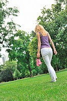 Yyoung woman holding her shoes and walking barefoot on grass in park _ rear view
