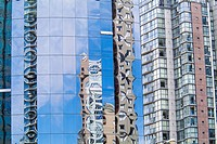 buildings are reflected in the glass of the Wall Centre tower in downtown Vancouver, BC, Canada