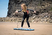 Girl in wetsuit playing with surfboard