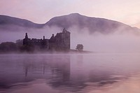 Reflection of Kilchurn Castle in Loch Awe lake in fog, Strathclyde, Scotland