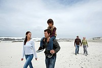 Three generation family walking on the beach