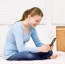 Young girl sitting on bed texting. Square framed shot