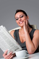 Thoughtful businesswoman read newspaper at office