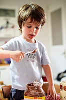 Child takes chocolate from the pot