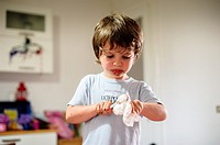 Child cleans his dirty spoon of chocolate